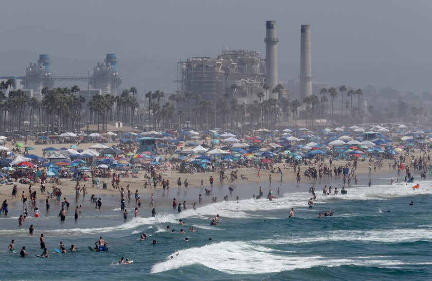 A Labor Day weekend crowd descends on Huntington Beach as a heat wave grips Southern California Saturday.