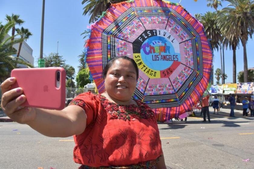 """Virginia Puac, de 49 años, originaria de la región maya cachiquel de Santiago Sacatepéquez (Guatemala) fue registrada este sábado al tomarse una foto frete a un tradicional barrilete (cometa) de Guatemala, en un área latina de Los Ángeles (EE.UU.), para celebrar la tercera edición del """"Festival Chapín"""" con el lema """"Recordando mis raíces"""". EFE/Iván Mejía"""