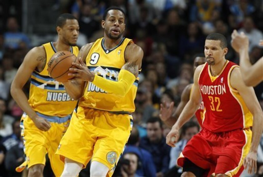 Denver Nuggets guard Andre Iguodala, front left, picks up a loose ball as Houston Rockets guard Francisco Garcia, of the Dominican Republic, covers in the first quarter of an NBA basketball game in Denver on Saturday, April 6, 2013. Nuggets forward Anthony Randolph, rear, watches. (AP Photo/David Zalubowski)