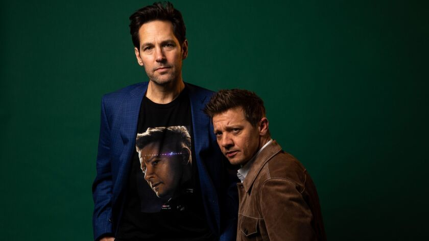 """Jeremy Renner, right, poses next to his own face, on a T-shirt worn by his """"Avengers: Endgame"""" costar Paul Rudd."""