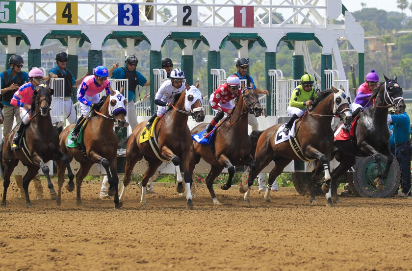 Horses break from the gate for the third race on opening day at Del Mar.