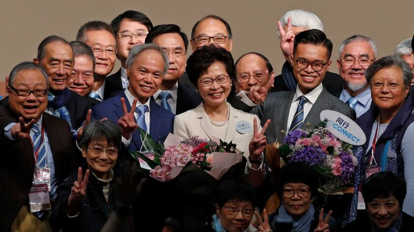 Former Hong Kong Chief Secretary Carrie Lam, center, smiles as she is congratulated by her supporter