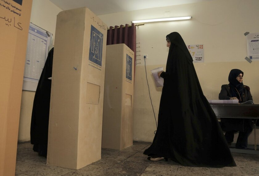 An Iraqi woman prepares to casts her vote at a polling station in Baghdad, Iraq, Wednesday, April 30, 2014. A key election for a new Iraqi parliament was underway on Wednesday amid a massive security operation as the country continued to slide deeper into sectarian violence more than two years after U.S. forces left the country. (AP Photo/ Khalid Mohammed)