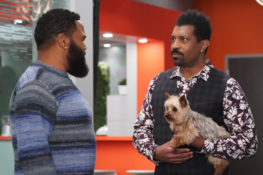 Two men, one holding a small dog, face each other.