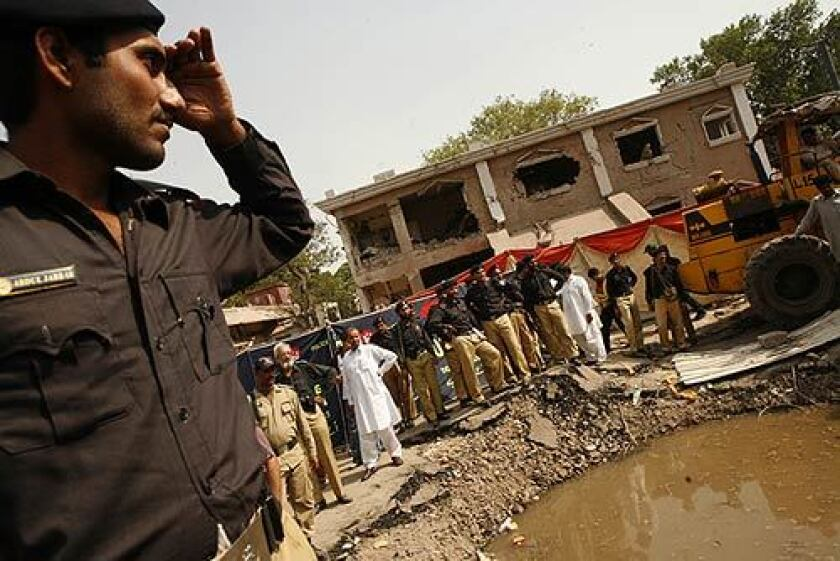 Officers in Lahore, Pakistan, survey the scene outside their precinct, called Rescue 51, where a car bomb was detonated. Thirty people were reported killed, and 250 injured.