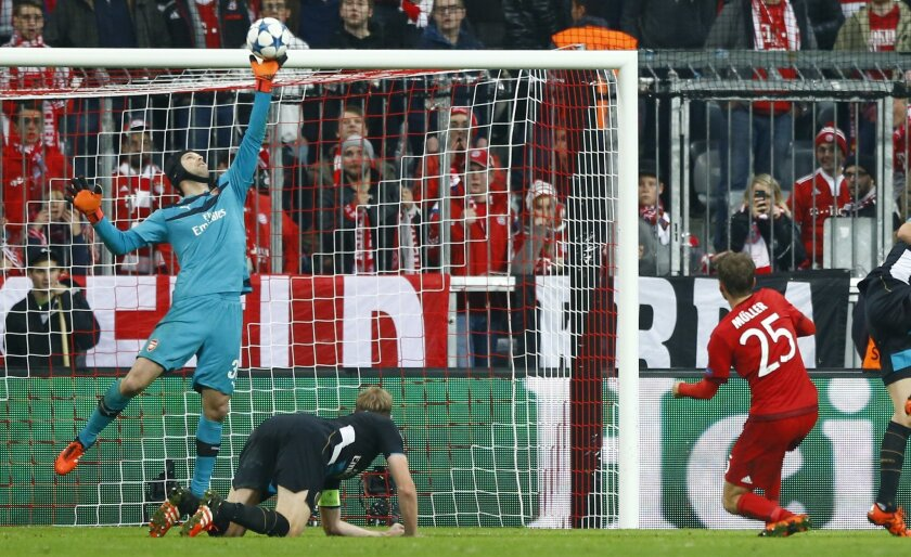 Arsenal goalkeeper Petr Cech, left, deflects a shot by Bayern's Thomas Mueller, right, during the Champions League Group F soccer match between Bayern Munich and Arsenal FC in Munich, southern Germany, Wednesday, Nov. 4, 2015. (AP Photo/Matthias Schrader)