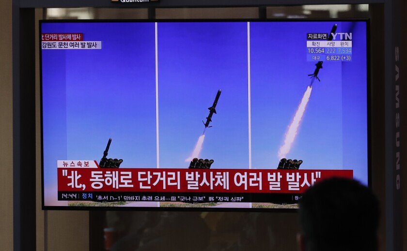 People at Seoul's railway station watch a TV airing reports of North Korean missiles. The reports use file images of missiles.