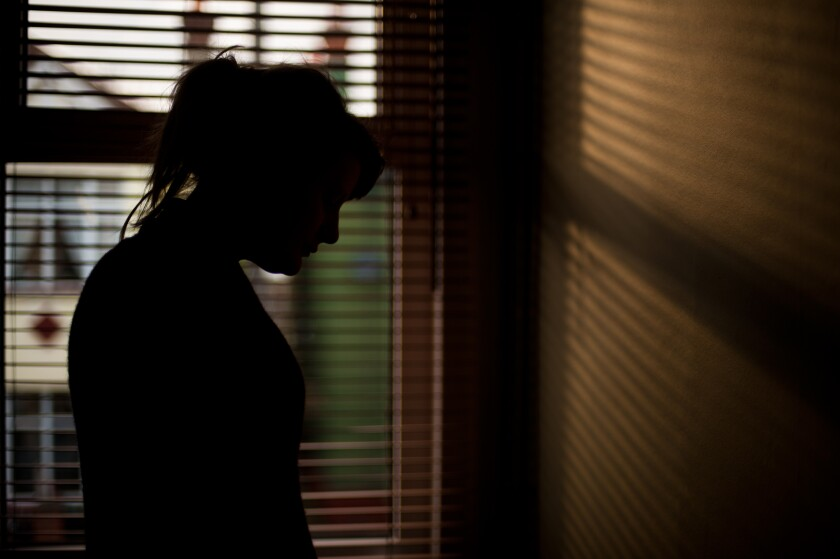 Silhouette of a woman standing by a window.