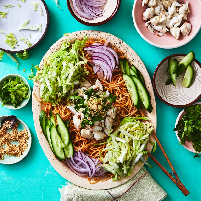 Chilled Sichuan noodles maintain all their chile warmth, without the chile sting, when made at home with chile crisp and sesame paste in the dressing and loads of crunchy vegetables and creamy crab on top. Prop styling by Nidia Cueva.