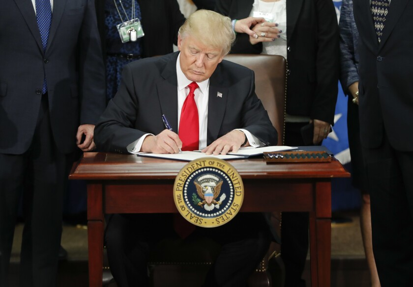 President Donald Trump signs an executive order for border security and immigration enforcement improvements at the Department of Homeland Security in Washington on Jan. 25, 2017.