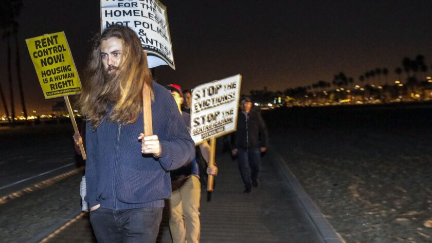 Protesters march on the beach in Belmont Shore to oppose the predawn homeless patrol.