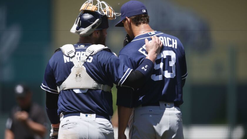 Padres catcher Derek Norris (3), left, confers with starting pitcher Christian Friedrich (53) in the first inning of a baseball game Sunday, June 12, 2016, in Denver.