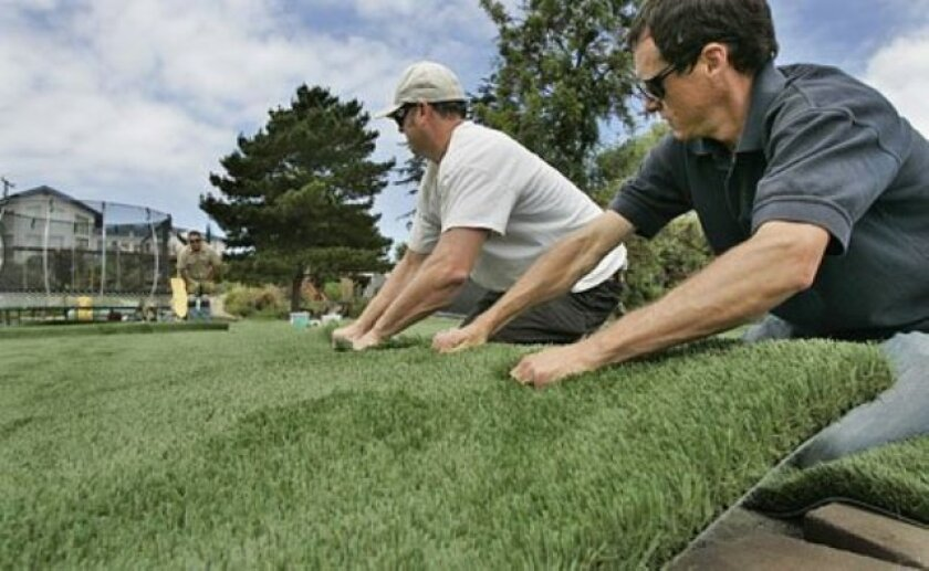 Moises Tapia (far left), Sam Reel (center) and Wes Darby installed artificial grass. Synthetic turf has grown in popularity among consumers who want to reduce water use. (Eduardo Contreras / Union-Tribune)