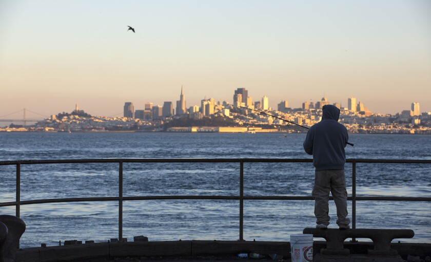 A fisherman tries the water off a pier in Horseshoe Bay with the San Francisco skyline as a backdrop.