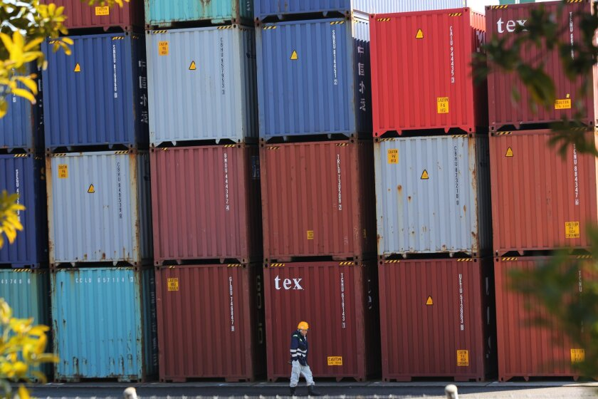 """FILE - In this Feb . 19, 2015 file photo, a port worker walks past a pile of cargo at a container terminal in Tokyo. The """"tankan"""" index for large manufacturers fell to 6 in March 2016, down from 12 in December. The Bank of Japan released the results of its quarterly survey on Friday. Japan's big exporters have been hit by a double whammy of a slowing Chinese economy and a rising yen. (AP Photo/Eugene Hoshiko, File)"""