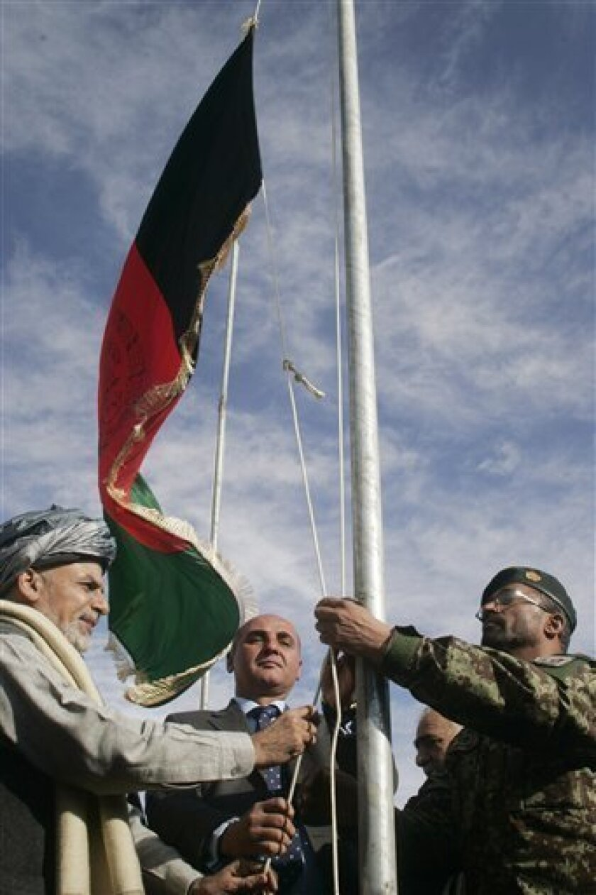 Ashraf Ghani Ahmadzai, left, head of the Transition Commission, raises the Afghanistan flag during the transfer of authority from NATO troops to Afghan security forces in Chaghcharan, Ghor province, west of Kabul, Afghanistan, Wednesday, Jan. 4, 2012. The security responsibilities of Chaghcharan, the provincial capital of Ghor province is handed over from the NATO forces to Afghan security forces. The process of taking over security from over 130,000-strong NATO-led ISAF forces by Afghan troops would be completed by the end of 2014 when Afghanistan will take over the full leadership of its own security duties from U.S. and NATO forces. (AP Photo/Hoshang Hashimi)