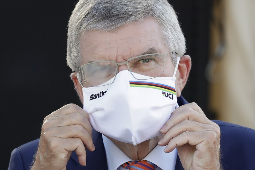 IOC President Thomas Bach waits for the podium ceremony for the women's elite event at the road cycling World Championships in Imola, Italy on Sept. 26, 2020. Organizers of a South Korean award say International Olympic Committee President Thomas Bach has decided not to visit in person this week and accept the prize because of concerns about the coronavirus pandemic. Bach was named winner of the Seoul Peace Prize last month and was to receive the award on Monday, Oct. 26, 2020. (AP Photo/Andrew Medichini)