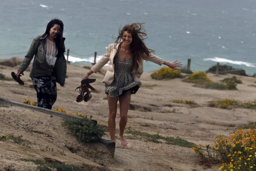 College friends Audrey Leung, 20, left, and Makenzie Lowe, 21, from UCSD thought they could get some nice photos of their fashion ideas for their new blog about thrifty fashions but the wind was a bit too daunting for the task Monday morning at the San Diego Gliderport.