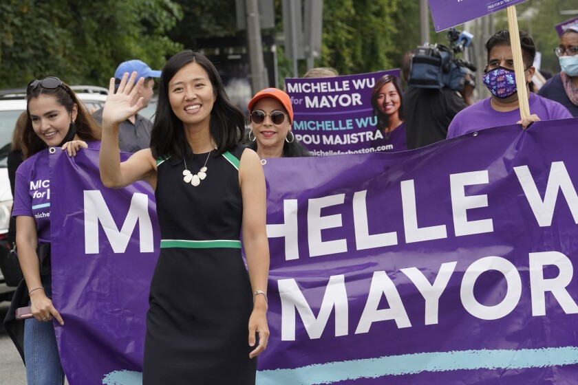FILE— In this July 18, 2021 file photograph, Boston mayoral candidate Michelle Wu waves while walking in the Roxbury Unity Parade, in Boston's Roxbury neighborhood. With Boston's preliminary mayoral election just a month off, voters are on the verge of making a historic decision by narrowing the field of five major candidates, all of whom are people of color. Since it first started electing mayors nearly 200 years ago, Boston has only tapped white men to lead the city — a streak certain to end this year, a reflection in part of the city's changing demographics. (AP Photo/Steven Senne, File)