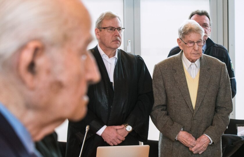 94-year-old former SS guard at the Auschwitz death camp Reinhold Hanning, right, stands next to his lawyer Andreas Scharmer, center, during his trial in Detmold, Germany, Friday, Feb. 12, 2016. Hanning faces trial for 170,000 counts of accessory to murder, the first of up to four cases being brough