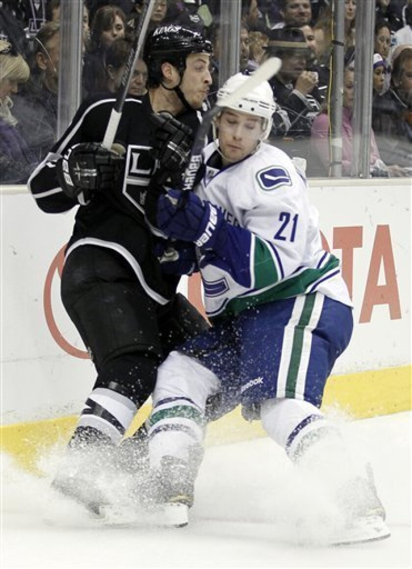 Vancouver Canucks left wing Mason Raymond, right, checks Los Angeles Kings defenseman Randy Jones during the first period in Game 6 of a first-round NHL hockey Western Conference playoff series in Los Angeles, Sunday, April 25, 2010. (AP Photo/Chris Carlson)