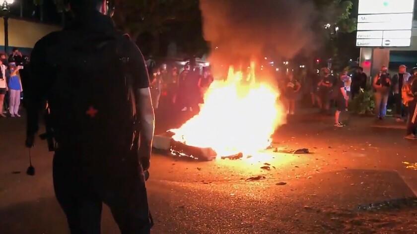 A mattress burns in the street near the Portland Police Bureau's North Precinct