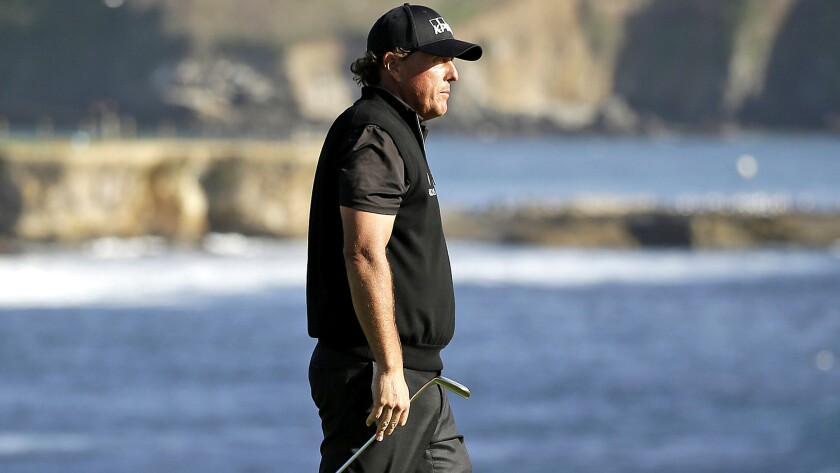 Phil Mickelson looks out at the ocean after missing a birdie putt on the 18th green Sunday at Pebble Beach.
