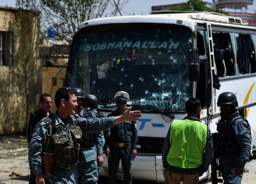 Afghan security personnel inspect the scene of a suicide attack on a bus in Kabul that was transporting government employees. Taliban attacks on Monday also killed 17 policemen in remote Badakhshan province.