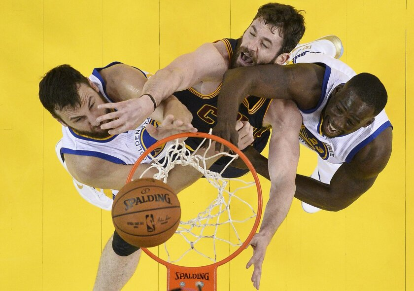 Cleveland Cavaliers forward Kevin Love, center, reaches for the ball between Golden State Warriors center Andrew Bogut, left, and forward Draymond Green during the first half of Game 2 of basketball's NBA Finals in Oakland, Calif., Thursday, June 2, 2016. (John G, Mabanglo, European Pressphoto Agen