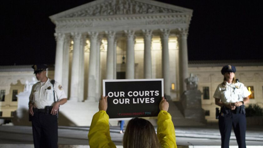 A demonstrator protests in front of the Supreme Court as President Trump announces his nomination of Brett Kavanaugh to the bench on July 9.