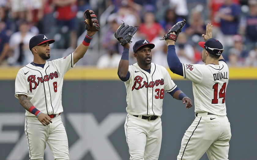 Atlanta Braves outfielders, from left to right, Eddie Rosario (8), Guillermo Heredia and Adam Duvall (14) celebrate at the end of a baseball game against the New York Mets, Sunday, Oct. 3, 2021, in Atlanta. (AP Photo/Ben Margot)