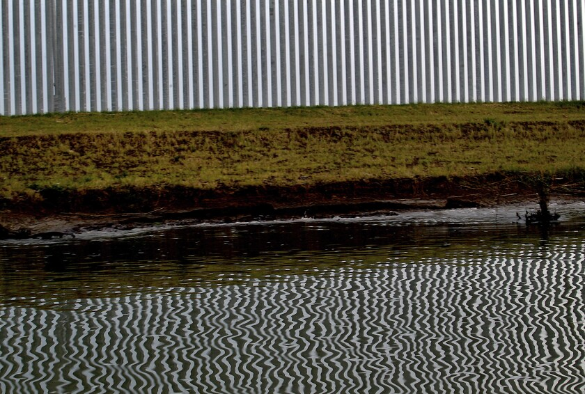 FILE - The reflection of a private border wall is seen on the glassy waters of the Rio Grande on Monday, April 5, 2021 in Mission, Texas. South Texas officials say they are worried about flooding during the hurricane season starting June 1 from breaches in a levee system that remain after border wall construction was halted. Hidalgo County Judge Richard Cortez told Border Report Wednesday, April 14, 2021 that there are at least four breaches in the levee system protecting Hidalgo County's low-lying region from floods during a major storm. (Delcia Lopez/The Monitor via AP, file)