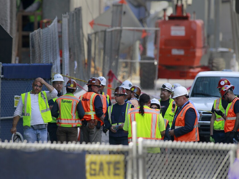 Construction workers gather near the area where an electrician died after falling 53 floors from the Wilshire Grand construction site in downtown Los Angeles.