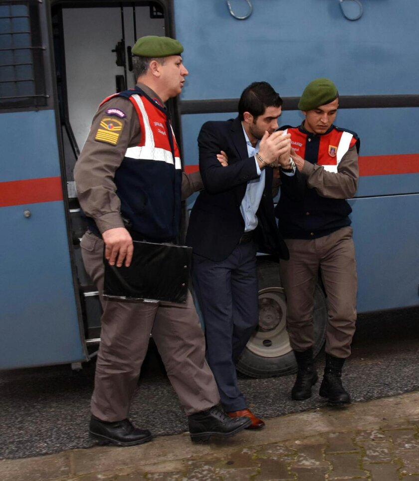 Prison guards escort Asem Alfrhad before his trial in Aegean resort of Bodrum, Turkey, Thursday  Feb. 11, 2016. Two alleged people-smugglers are on trial accused of causing the death of 3-year-old Syrian migrant boy Aylan Kurdi and four other people. The image of the boy — his lifeless body lying f