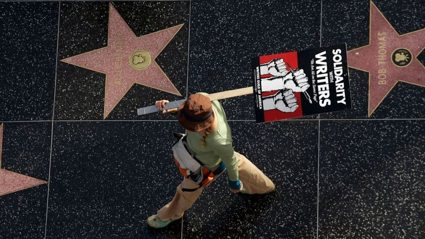 A picketer walks along the Walk of Fame on Hollywood Boulevard in 2007 during the Writers Guild of America strike that lasted 100 days.