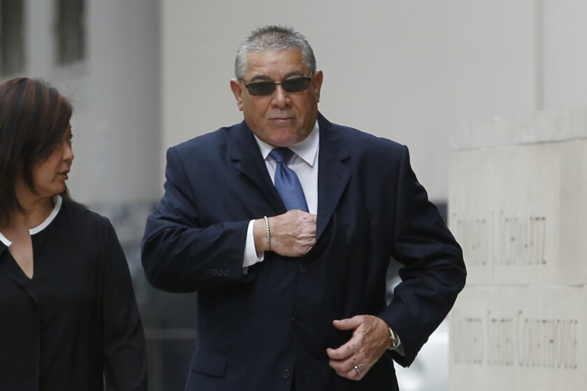 """Natividad """"Nate"""" Cervantes, known as the """"Godfather of Camp Pendleton,"""" walks into federal court in San Diego, where he pleaded guilty to taking bribes from defense contractors. The woman on his right is unidentified."""