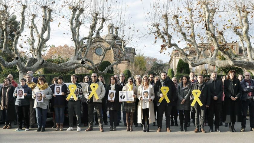 Catalan regional Parliament staff members and pro-independence MPs, displaying yellow ribbons and the portraits of imprisoned Catalan pro-independence political and social leaders, in a demonstration last month in Barcelona.