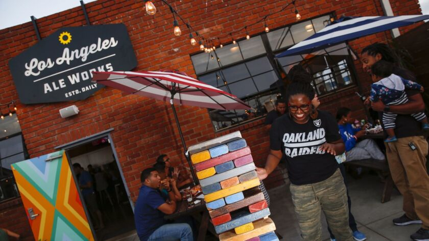 Sade Cooper works on an oversized Jenga game on the patio of Los Angeles Ale Works.