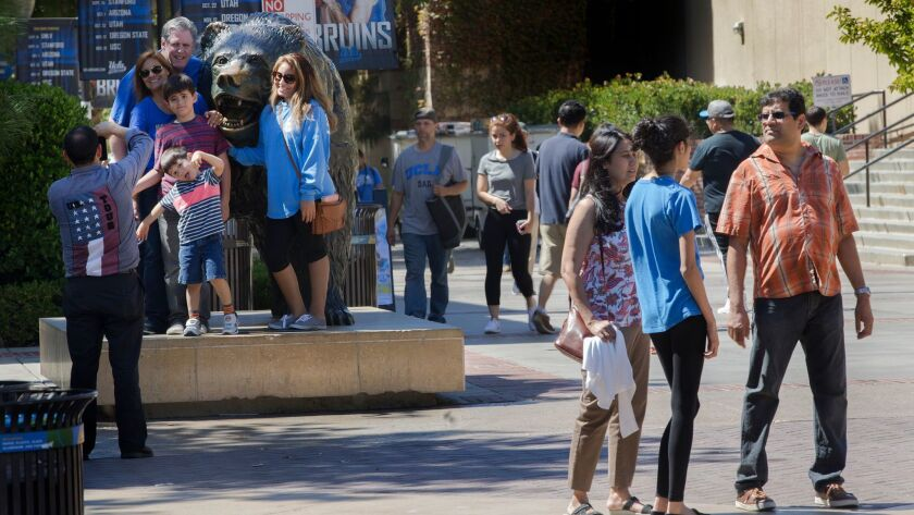 WESTWOOD, CA - SEPTEMBER 15, 2016: A family poses for a photo with the Bruin bear as students tour c