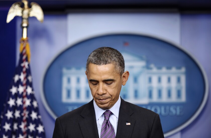 President Obama pauses as he makes a statement at the White House regarding the death of former South African President Nelson Mandela.