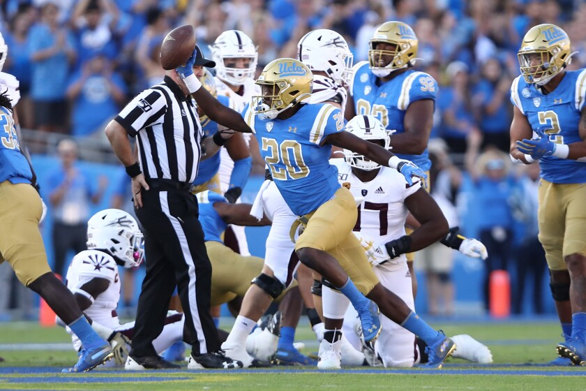 UCLA defensive back Elisha Guidry holds up the ball after recovering a fumble during the first half of a game against Arizona State.