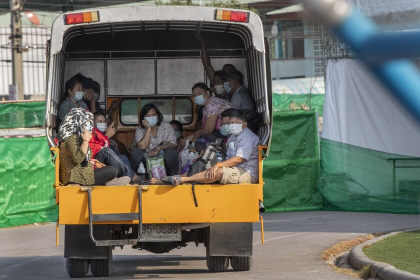 Migrant workers and their families ride in the back of a truck as they wait to be admitted to a field hospital for COVID-19 patents, Monday, Jan. 4, 2021, in Samut Sakhon, South of Bangkok, Thailand. Thailand reported on Tuesday, Jan. 5, 2021, over 500 new coronavirus cases, most of them migrant workers who already were isolated, and the government said it was tightening movements of people around the country. (AP Photo/Gemunu Amarasinghe)