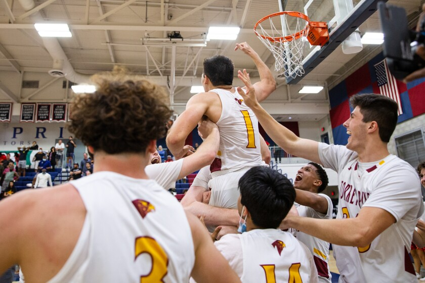 Torrey Pines High School's Nick Herrmann (1) is lifted in celebration.