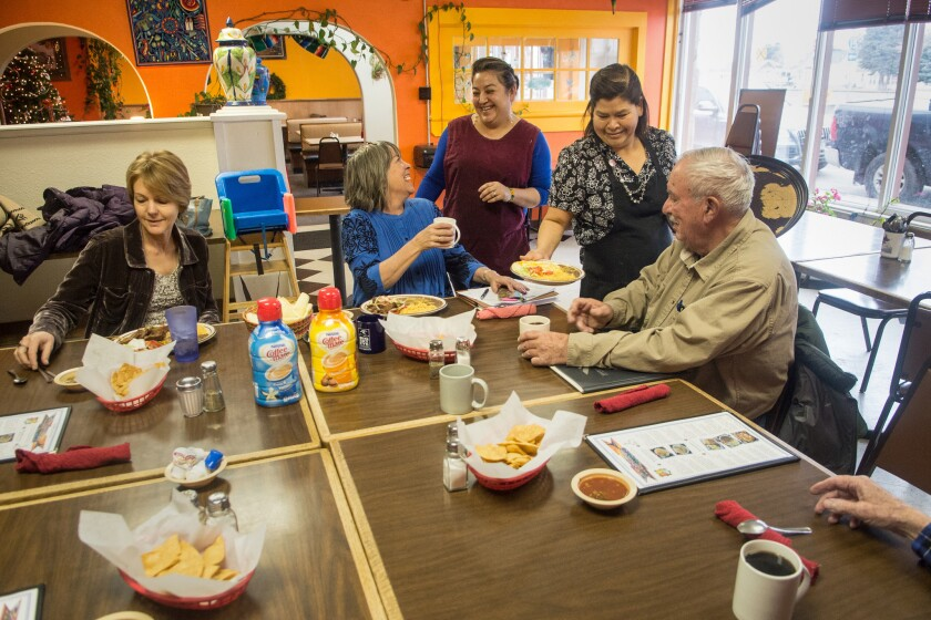 Yeni Mora visits with some of her regular customers as Maria Cervantes serves them at Los Koritas, Mora's Mexican restaurant in Dillon, Mont.