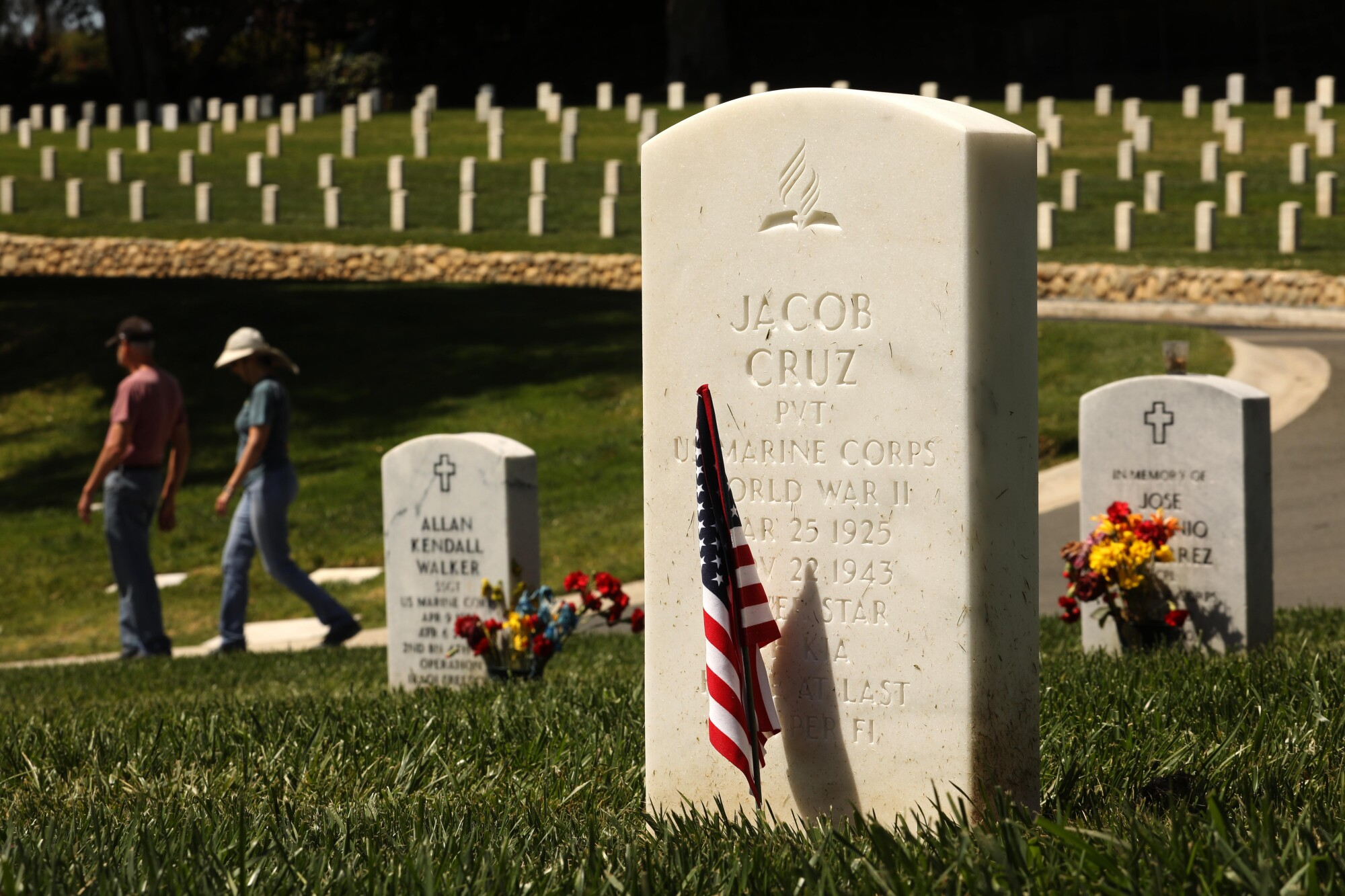 A tombstone with an American flag planted in front of it sits in a cemetery.