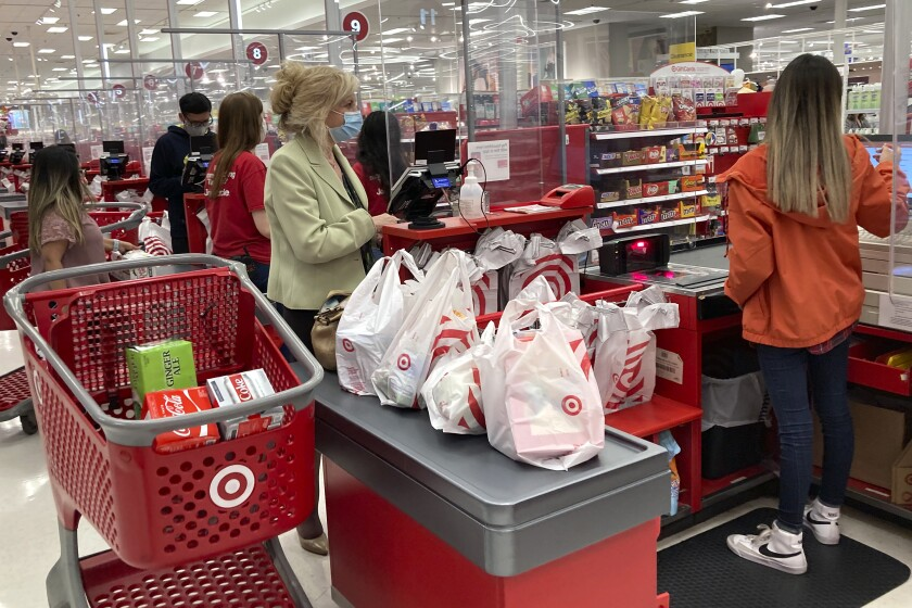 A customer wears a mask as she waits to get a receipt at a register in Target store in Vernon Hills, Ill., Sunday, May 23, 2021. Consumer spending was flat in May while incomes dropped for a second month as the impact of the government's individual impact payments waned. (AP Photo/Nam Y. Huh)