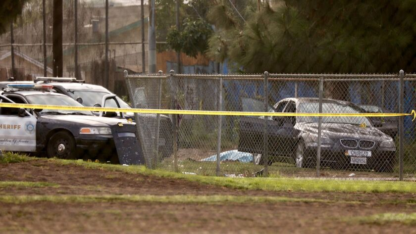 EAST LOS ANGELES CA SEPTEMBER 20, 2018 -- The body of a suspect lies near his vehicle following a d