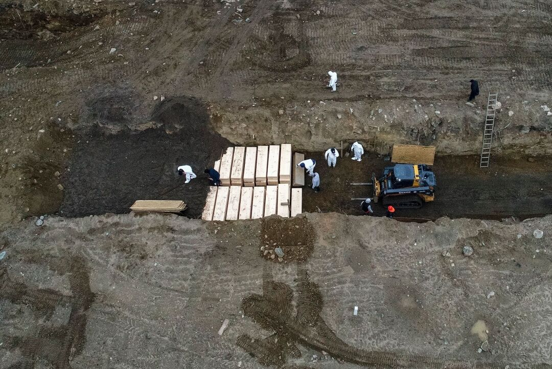 Workers wearing personal protective equipment bury bodies in a trench on Hart Island.