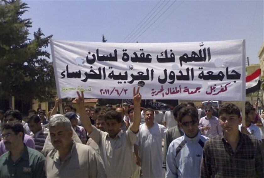 """In this citizen journalism image made on a mobile phone and provided by Shaam News Network, Syrian protesters hold an Arabic banner read:""""May God help break the silence of the Arab League,"""" as they march during a protest at the village of Kfar-Nebel, in the northen province of Edleb, Syria, on Friday June 3, 2011. Syrian troops pounded a central town with artillery and heavy machinegun fire Friday, killing at least two people in the latest onslaught as authorities cut off Internet service in several regions in an apparent move to prevent the uploading of videos of anti-regime demonstrations, activists said. (AP Photo/Shaam News Network) EDITORIAL USE ONLY, NO SALES, THE ASSOCIATED PRESS IS UNABLE TO INDEPENDENTLY VERIFY THE AUTHENTICITY, CONTENT, LOCATION OR DATE OF THIS HANDOUT PHOTO"""