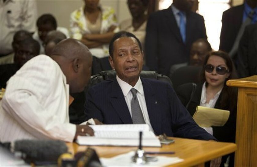 """Former Haitian dictator Jean-Claude Duvalier, known as """"Baby Doc,"""" center, attends his hearing as his companion Veronique Roy sits behind, right, inside a courthouse in Port-au-Prince, Haiti, Thursday, Feb. 28, 2013. Duvalier appeared in court Thursday after three times shunning a summons for a hea"""